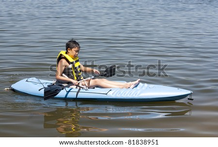 A young Korean boy in a Kayak on a lake - stock photo
