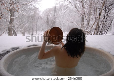 a young Korean woman in a hot open air onsen bath in the snowfield - stock photo