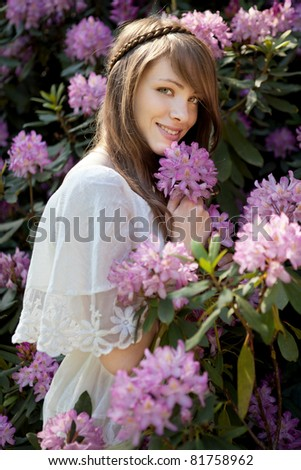 A young lady enjoys the smell of a rhododendron  blossom