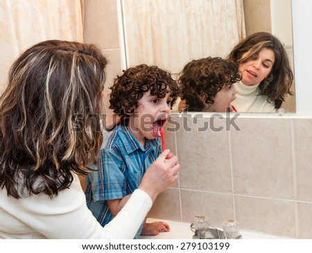 A young lady helping a small child clean his tongue with a toothbrush in bathroom in front of a large mirror, family everyday scene - stock photo