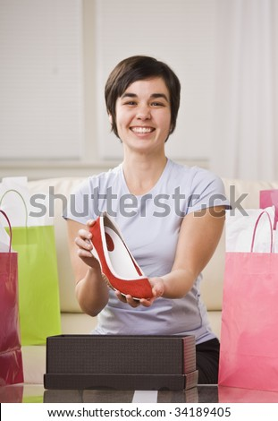 A young lady is holding up a shoe from a box and smiling at the camera.  She is surrounded by shopping bags.  Vertically framed shot. - stock photo