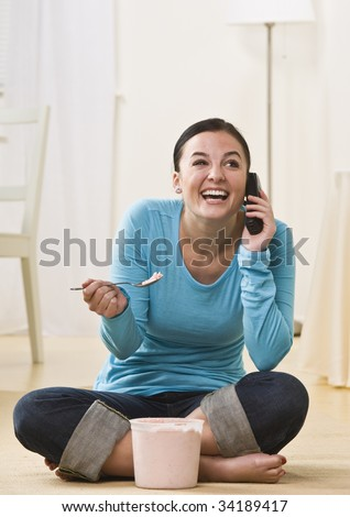 A young lady is talking on a telephone and eating ice cream.  She is smiling and looking away from the camera.  Vertically framed shot. - stock photo