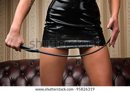 A young lady mistress with a whip, leather couch on background. - stock photo