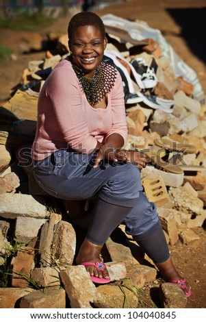 A young lady posing for the photographer on a load of bricks laying around. - stock photo