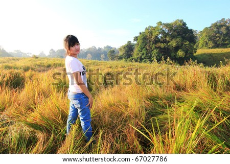 a young lady standing on grass field