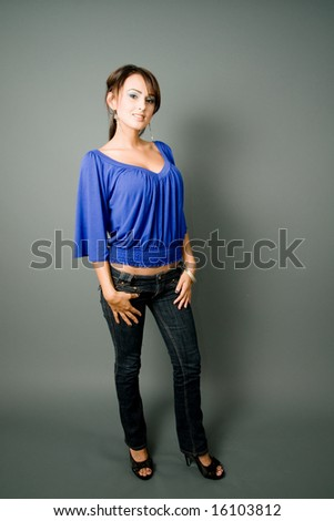 a young latin in blue blouse smiles in urban attire - stock photo