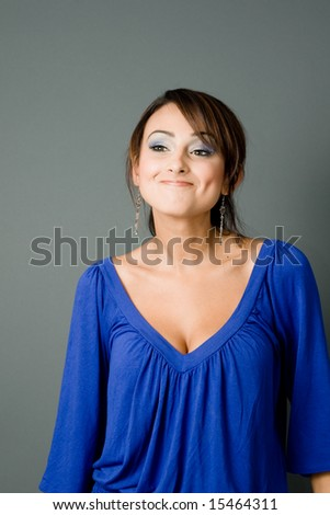 a young latin in blue blouse smiles without showing her teeth but with dimples - stock photo