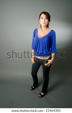 a young latina looks upwards and feels slightly bored. - stock photo
