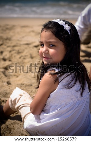 a young latino girl sitting on the beach near the shore