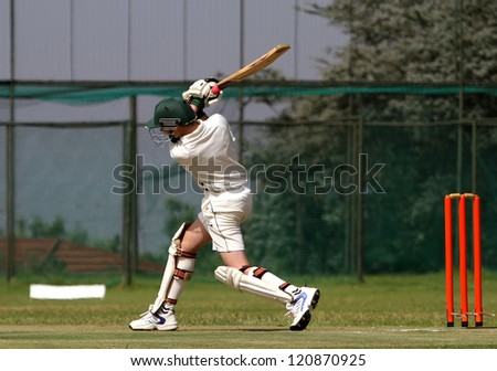 A young left hand cricket player drives the ball through the covers and ends with a beautiful follow-through - stock photo