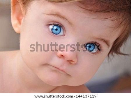 A young little baby is looking at the camera with bright blue eyes. Use it for a child or parenthood concept. - stock photo