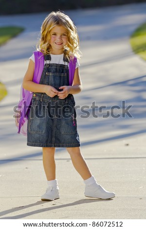 A young little girl preparing to walk to school - stock photo
