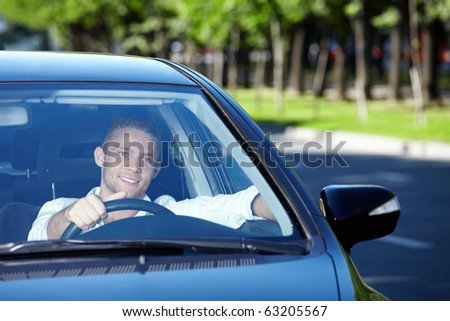 A young-looking man driving a car - stock photo