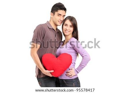 A young loving couple holding a red heart shaped pillow isolated on white background - stock photo