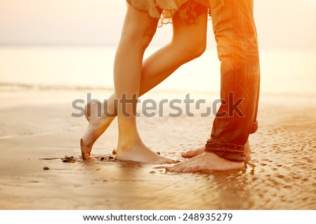 A young  loving  couple hugging and kissing on the beach at sunset. Two lovers, man and woman barefoot near the water. Summer in love  - stock photo