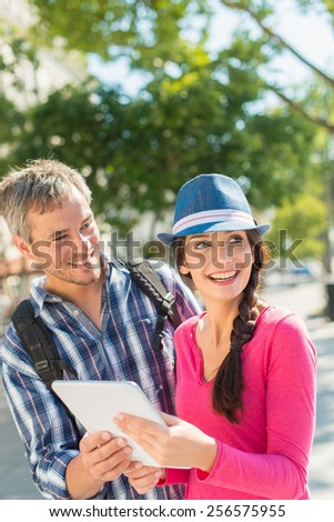 A young loving couple is holding a digital tablet in the city. The woman with the blue hat is looking at something away and the grey hair man with a beard is looking at her. Focus on them.