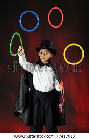 A young magician juggling colorful rings.  Some motion blur on the rings. - stock photo