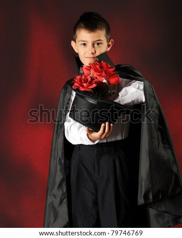 A young magician produces a big bouquet of red roses from his hat. - stock photo