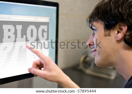 A young main pointing at a computer screen that reads BLOG in the web browser window.