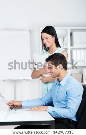 A young male and a charming female business executive looking at the computer screen in the office. - stock photo