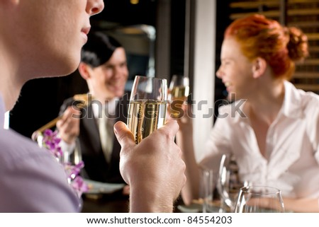 A young male and female couple giggle in the background of celebrations at a Japanese themed team lunch - stock photo