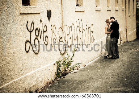 A young male and female expresses their passion for each other by kissing in an alley - stock photo