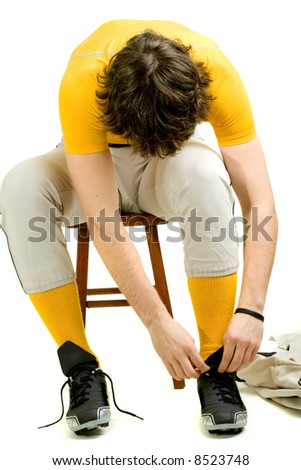 A young male baseball player sitting on a stool. - stock photo