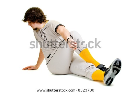A young male baseball player stretching.