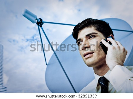 A young male businessperson on a cellular phone with satellite dish in background. - stock photo
