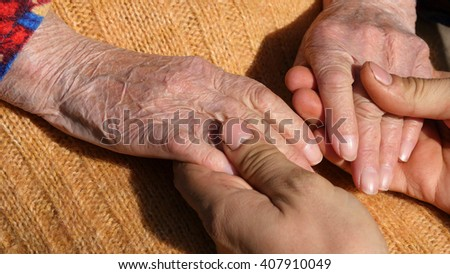 A young male hands comforting an elderly pair of hands of grandma outdoor close up.