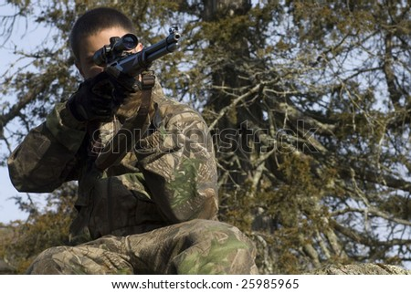 A young male hunter aims at his target - stock photo