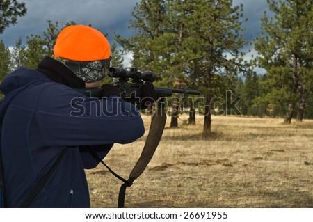 A young male hunter aims his rifle into the nearby woods. - stock photo