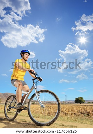 A young male in yellow shirt riding a bike on a sunny day in Macedonia - stock photo