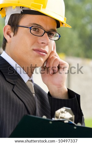 A young male manager in hard hat making a phone call - stock photo