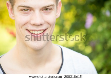 A young male model is laughing in a bright, green and beautiful garden - closeup, left