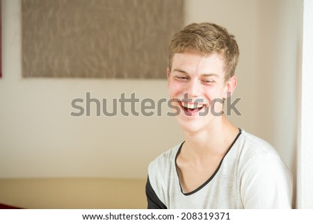 A young male model is laughing into the camera with a dark natural looking background - stock photo