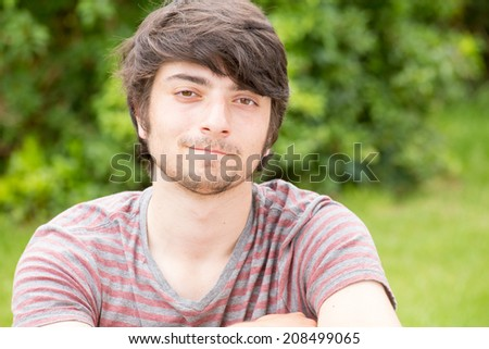 A young male model is looking into the camera happily while nodding his head slightly to the right - stock photo