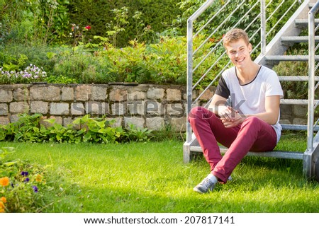 A young male model is sitting in a beautiful green garden during sunrise and enjoying the time while smiling a t the camera - stock photo
