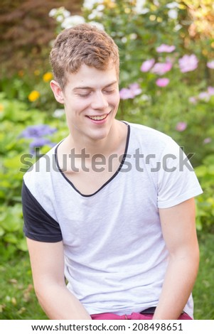 A young male model is sleeping upright in a bright, green and beautiful garden - stock photo
