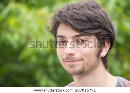 A young male model is smiling into the camera - stock photo
