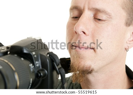 A young male photographer looks at the back of his camera at the photo he just took. - stock photo
