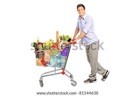 A young male pushing a shopping cart full with groceries isolated on white background - stock photo
