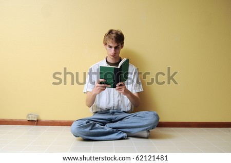 A young male reading a small hardcover book in an empty room with lots of copyspace around his body. - stock photo