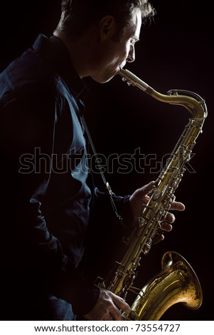 A young male saxophonist in a dark concert lit environment. - stock photo