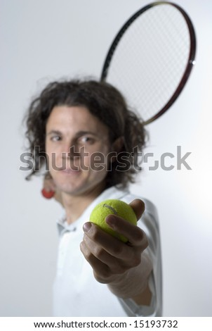 A young male serving a tennis ball.  He is looking at the camera, and he has a slight smile on his face.  Vertically framed shot. - stock photo