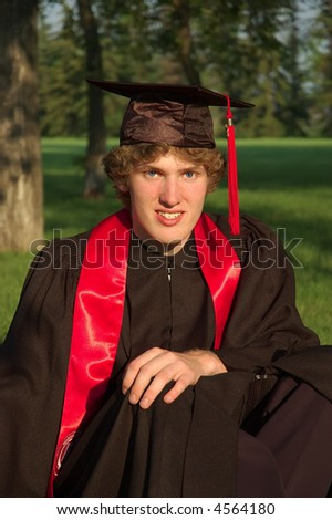A young male student in cap and gown, park like setting - stock photo