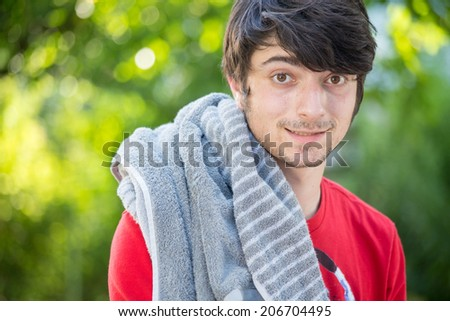 A young male student is feeling hot and looking into the camera