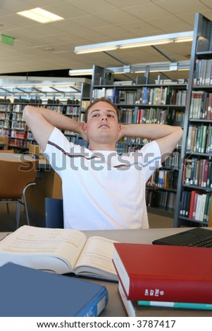 A young male student taking a break in th library