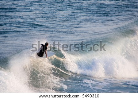 a young male surfer catching a wave