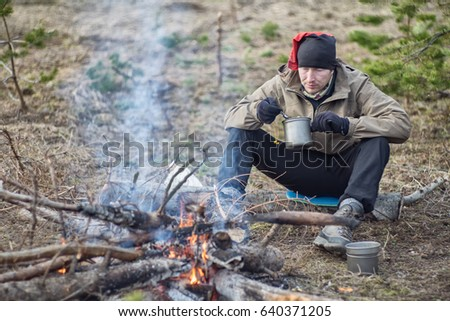A young male tourist at the fire in the forest is eating. Food in the campaign.